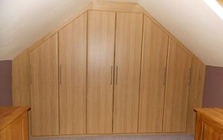 a beautiful wardrobe with hinged doors installed in a sloping loft space