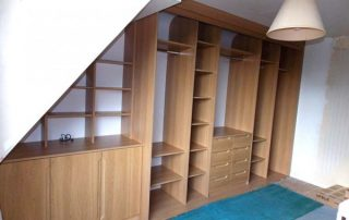 fitted wardrobe in a loft conversion in a cherry finish without doors