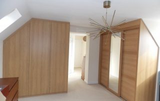 beautiful high-end timber fitted wardrobes with sliding doors in a prestigious loft conversion