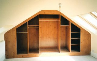 inside a knotty pine finished wardrobe with hinged doors custom fitted