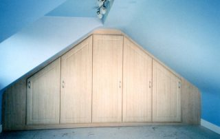 ash hinged wardrobe custom fitted in a loftspace with two sloping roof sections