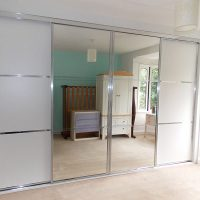white panels, chrome and mirrored sliding door wardrobe