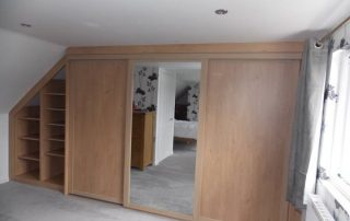 Floor to ceiling sliding wardrobe with mirrored door in reduced height sloping end of a loft conversion