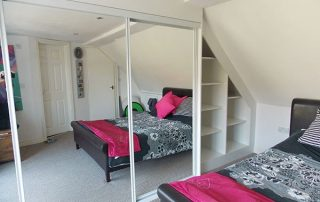 white and mirrored sliding wardrobe door in loft conversion