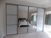 mirrored sliding wardrobe doors and white panelled wardrobe
